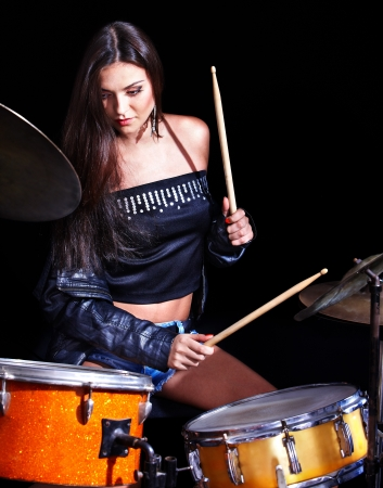 bass drum: Young woman playing  drum and cymbals in night club.