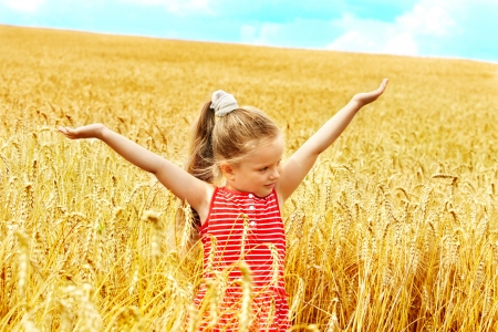 Happy little girl outdoor in wheat field. Summer.
