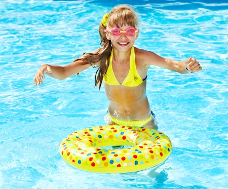 Little girl in swimming pool. Summer outdoor. photo