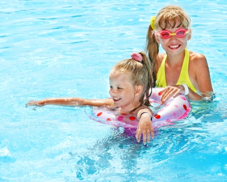 swimming float: Children playing with inflatable ring on water.