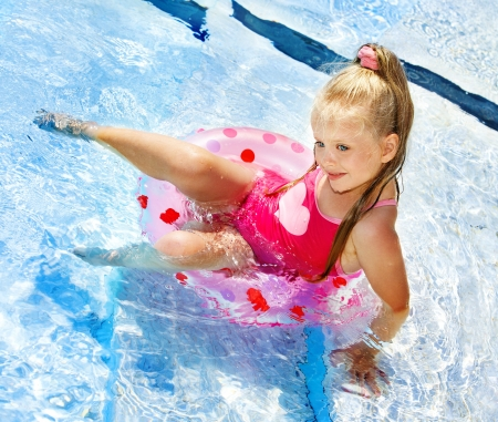 one piece swimsuit: Little girl sitting on inflatable ring in swimming pool.