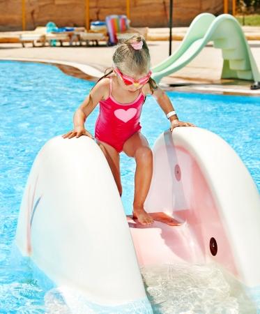 Child on water slide at aquapark. Summer holiday. photo