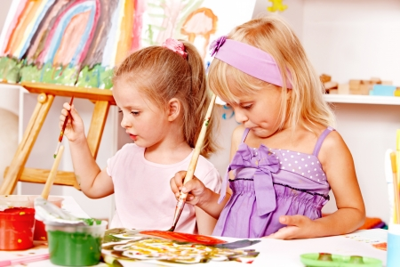 playschool: Child painting at easel in school. Education.
