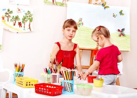 nurser: Children painting colour pencil in preschool.