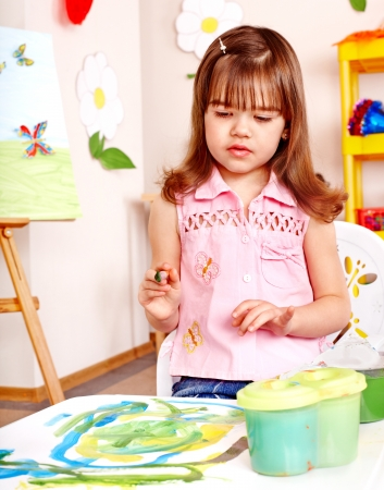 Little girl painting at easel in school. Stock Photo - 14752439