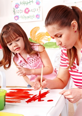 Child and teacher painting at easel in school. Stock Photo - 14742204