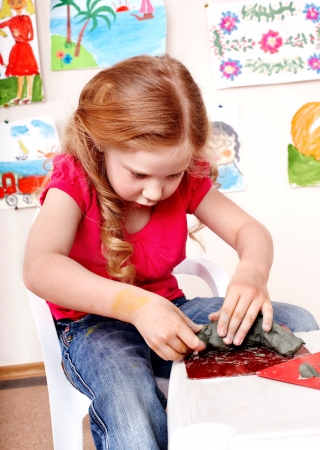 Child playing plasticine in kindergarten. Creativity development. photo