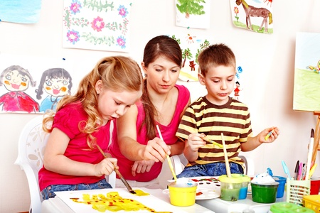 children painting: Happy child painting with teacher in school. Education.