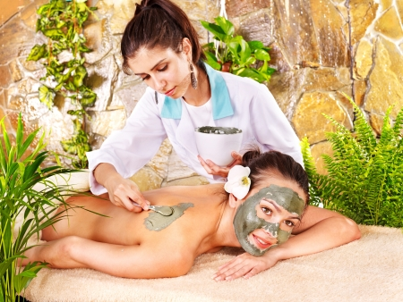 mud woman: Beautiful girl having clay facial mask apply by beautician. Stock Photo