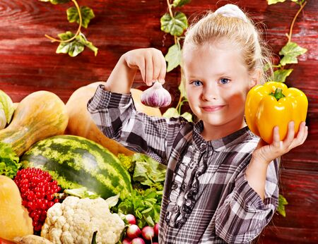 Little girl with vegetable on Rustic kitchen photo