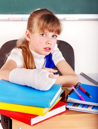 arm in arm: Child with broken arm in classroom. Stock Photo