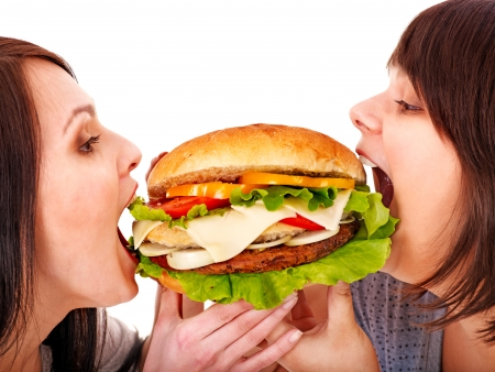 high calorie foods: Women eating hamburger. Isolated.