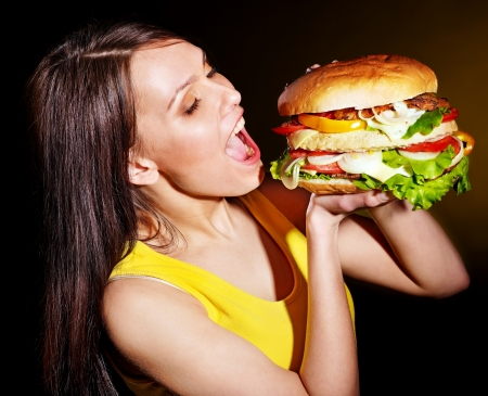 eating out: Slim woman bite big hamburger. Stock Photo
