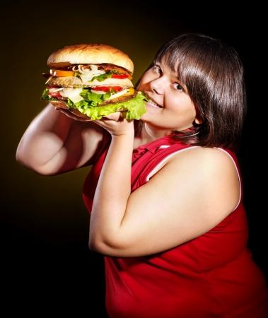 fatty food: Hungry woman eating big hamburger. Stock Photo