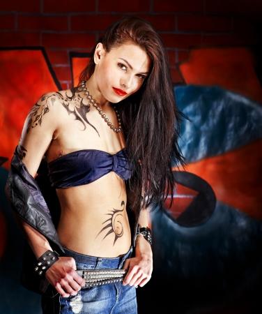 body paint: Mujer joven con el arte corporal pared de ladrillo aganist graffiti. Foto de archivo