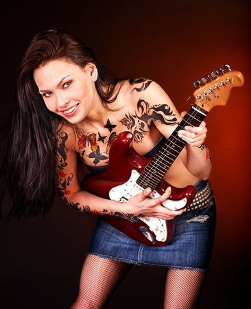 Aggressive young woman with tattoo playing guitar. photo
