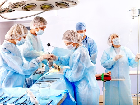 surgical coat: Group people surgeon at work in operating room. Stock Photo