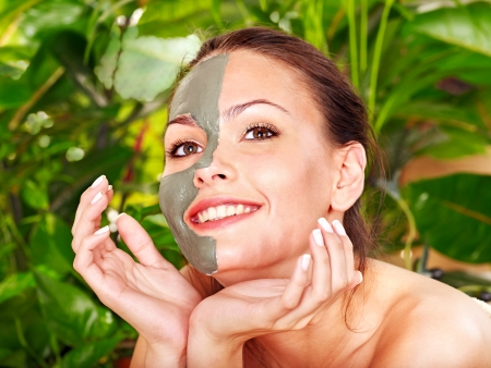 mud woman: Happy woman getting facial mask in tropical beauty spa. Stock Photo