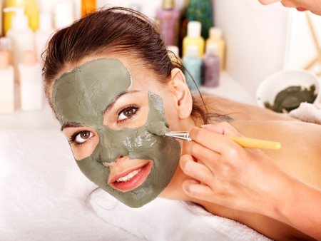 Woman with clay facial mask in beauty spa. Stock Photo - 14743304
