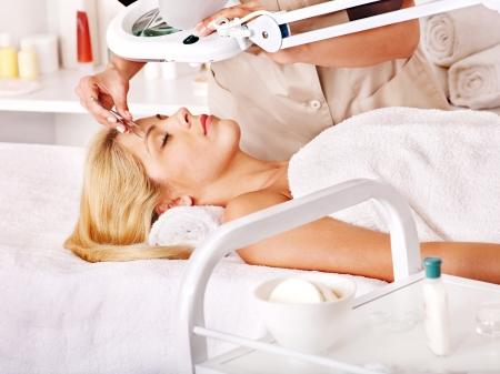 tratamiento facial: Mujer recibiendo las cejas depilación con pinzas por la esteticista. Foto de archivo