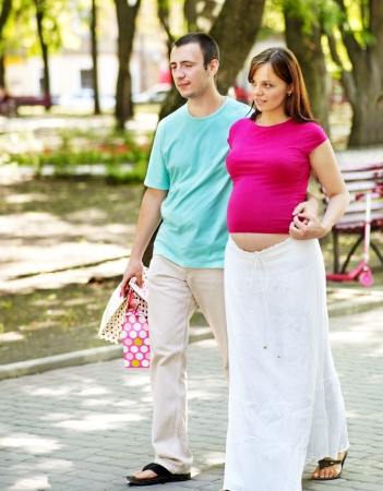 enceinte: Pregnant couple holding shopping bag outdoor.