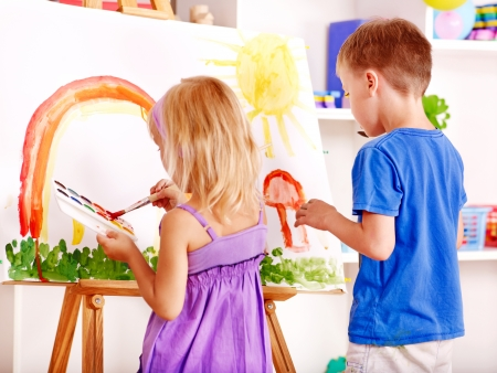 art activity: Child girl and boy painting at easel in school.
