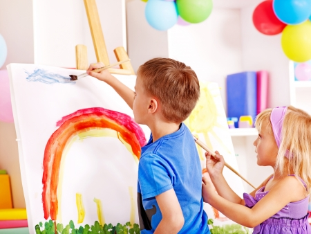 Two child painting at easel in school. Education.