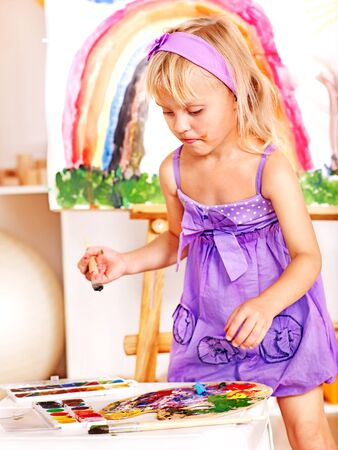 Little girl painting at easel in school. Education. photo