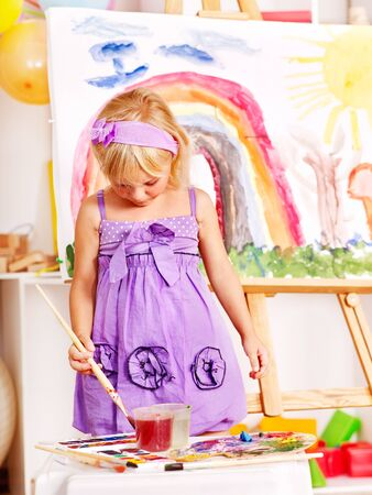 kids club: Little girl painting at easel in school. Stock Photo
