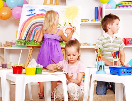 preschool education: Group children painting at easel in school. Stock Photo
