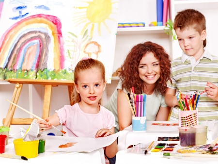 nursery education: Child with teacher painting at easel in school. Stock Photo