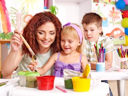 maestra preescolar: Los niños con la pintura de caballete profesor en la escuela. Foto de archivo