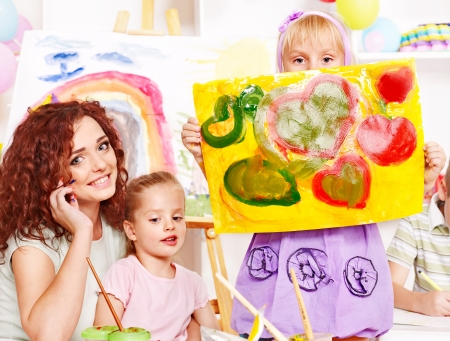 Child girl and teacher painting  in school. photo