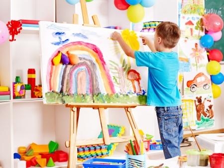 artist painting: Child painting at easel in school. Education.