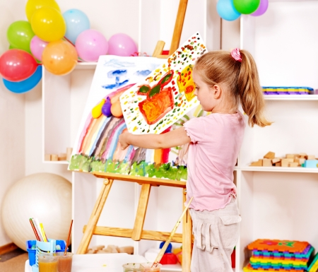playschool: Child painting at easel in school. Stock Photo
