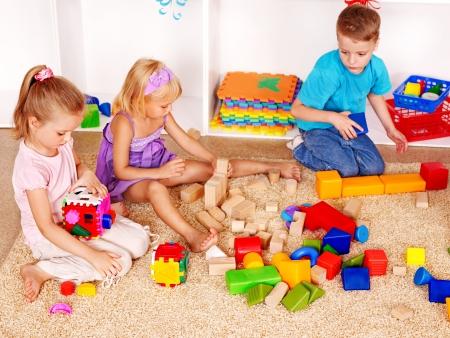 nursery education: Ni�a y ni�o de jard�n de infantes en el bloque de apilamiento.