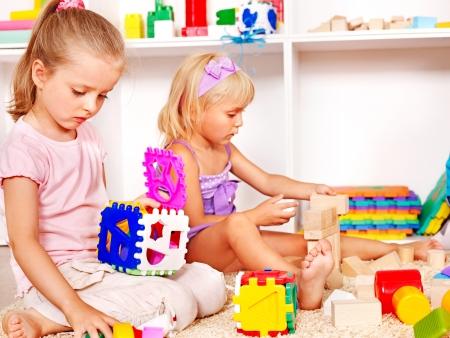 play school: Children in kindergarten stacking block.