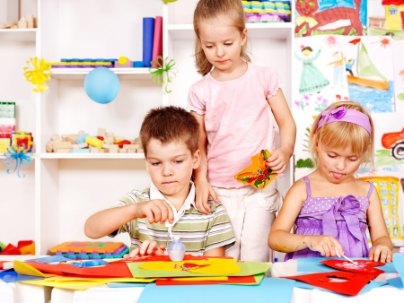 nursery school: Child boy cutting out scissors paper in preschool.