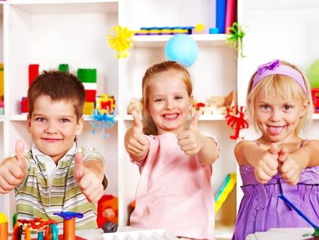 play of color: Group of children  in preschool thumb up. Stock Photo