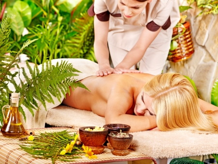 Woman getting back massage in tropical spa. Stock Photo - 14751669