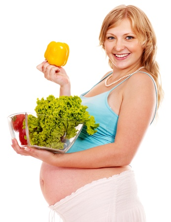 enceinte: Pregnant woman eating vegetable. Isolated. Stock Photo