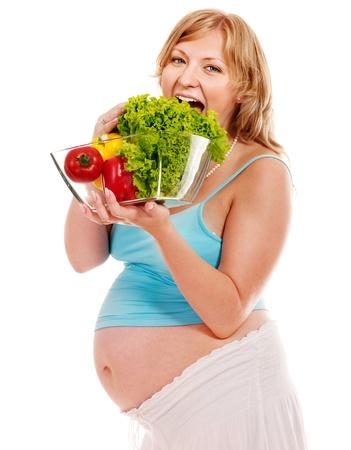 vientre femenino: Mujer embarazada que come vegetales. Aislado.