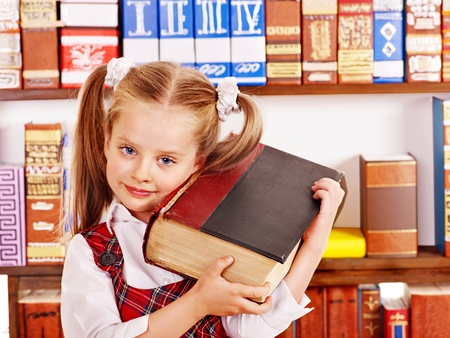 Happy child holding book in library. photo