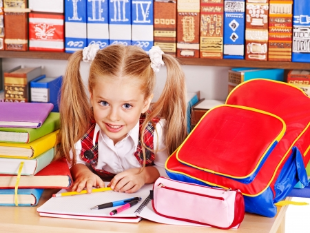 Happy child with backpack holding book. Isolated. photo