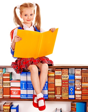Happy child holding book near bookshelf.