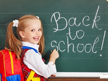first class: Happy schoolchild writting on blackboard.