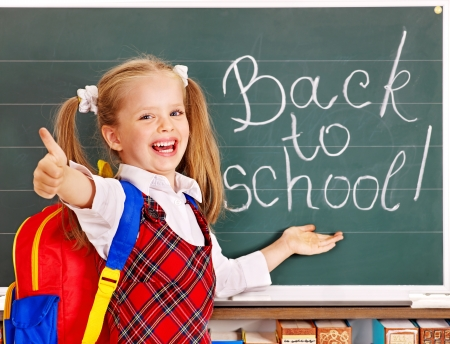 school children uniform: Happy child with backpack holding book. Isolated.