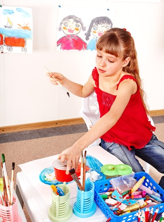 nurser: Little girl with picture and brush in playroom. Stock Photo