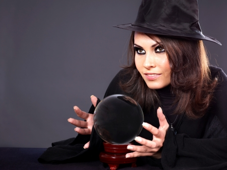 Woman wearing witch hat with crystal ball. Fortune telling. photo