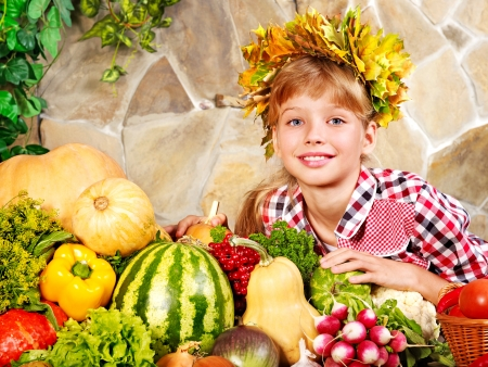 Little girl with vegetable on kitchen at home. photo